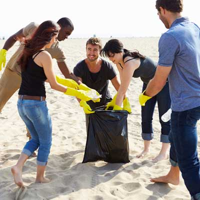 group of people picking garbage off a beach
